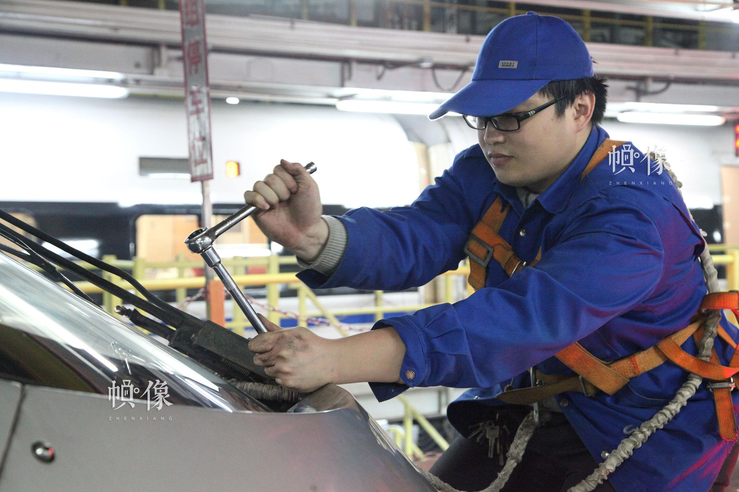 图为作业人员姜宇航更换雨刷器。北京动车段 李博 供图