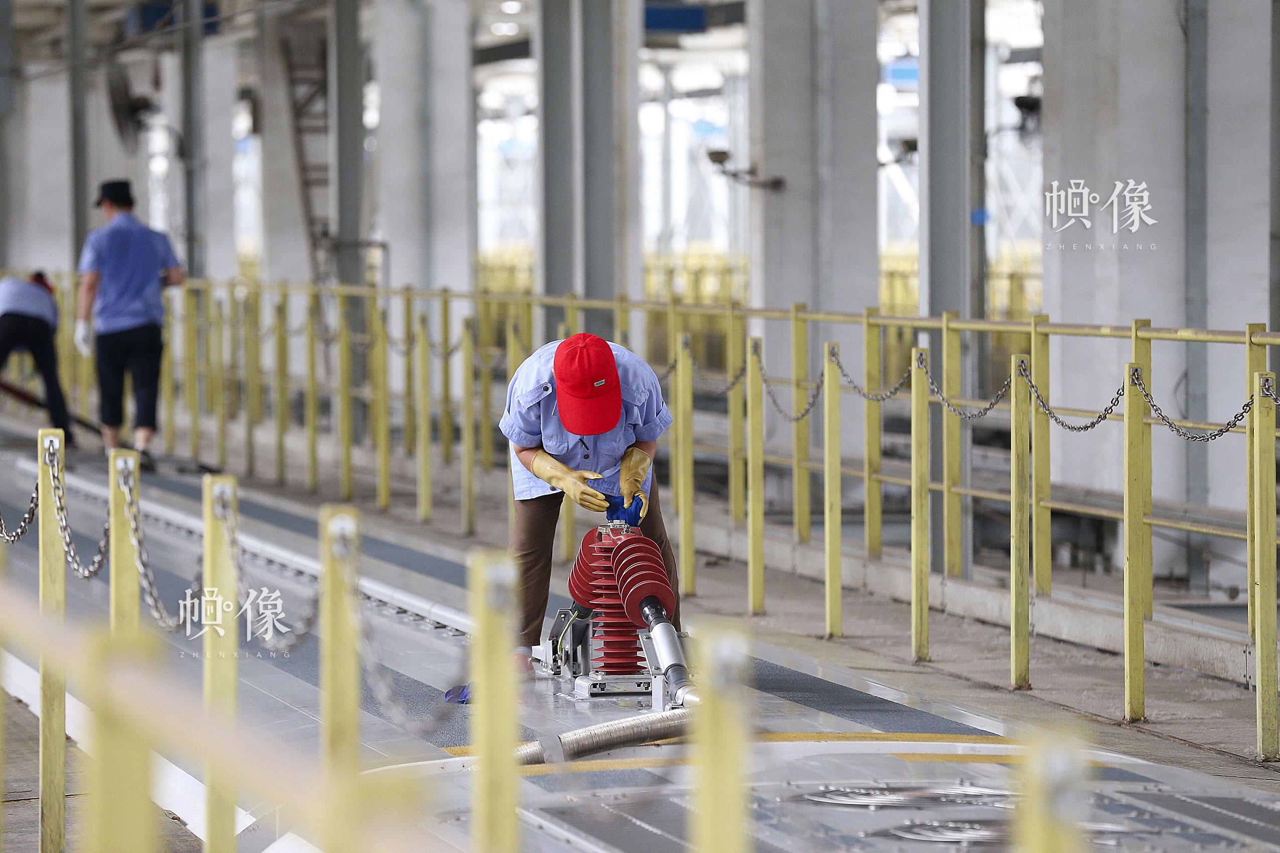 工作人员擦洗车顶电力设备。中国网记者 黄富友 摄