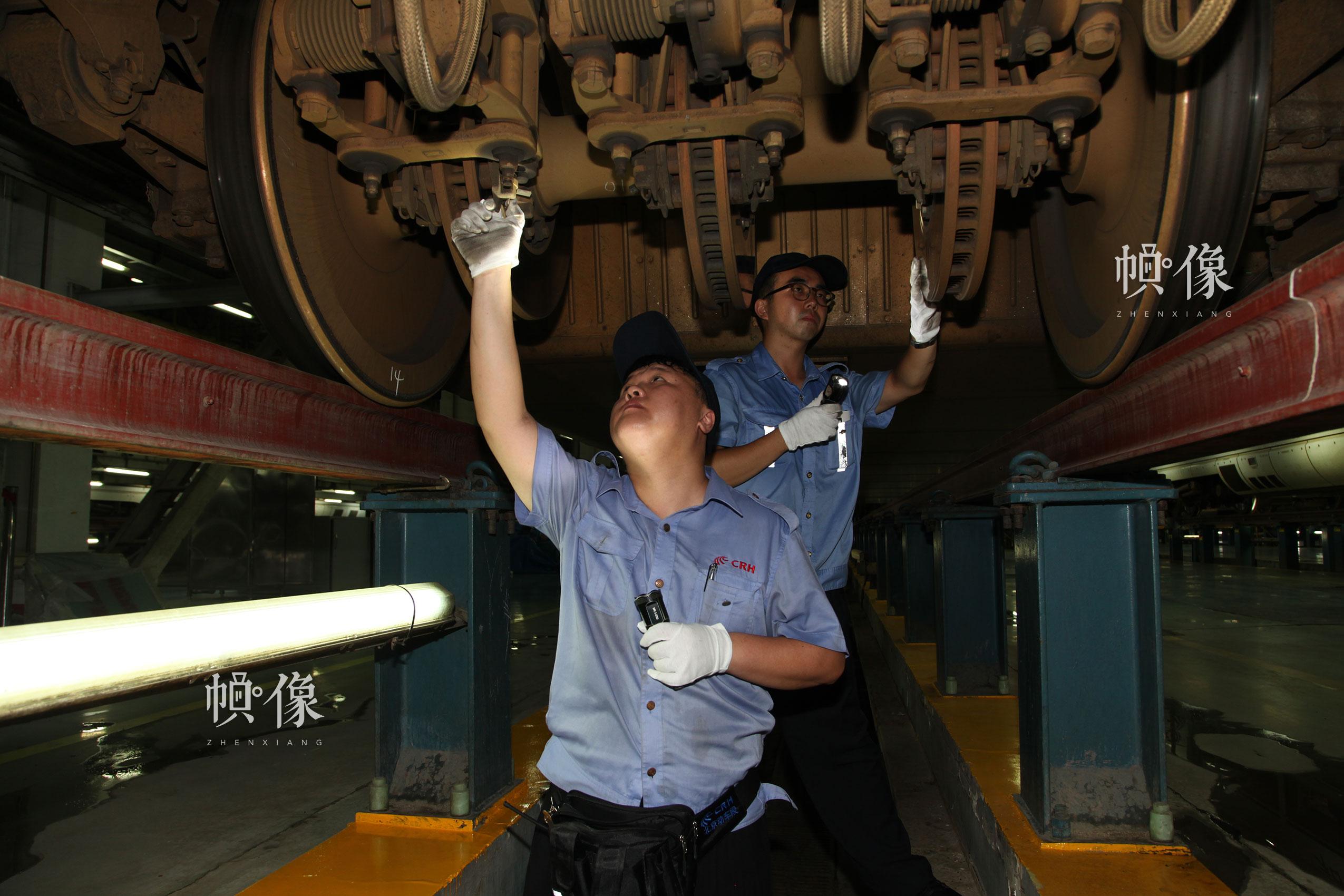 作业人员对车底转向架进行检修。北京动车段 李博 供图