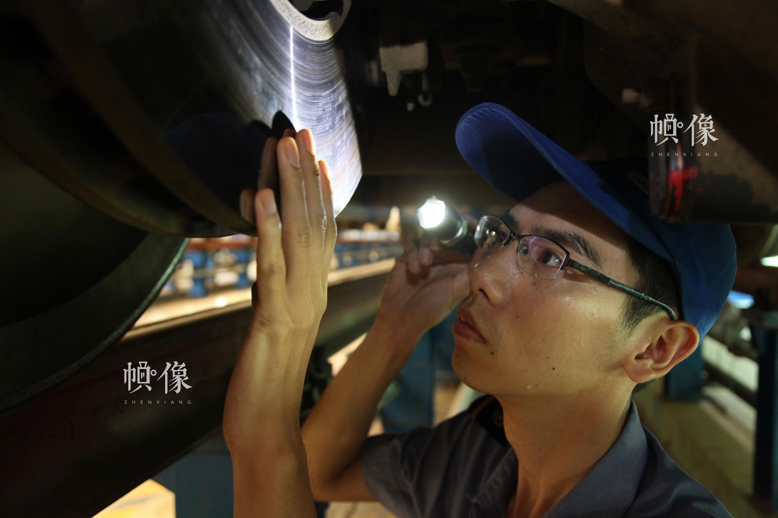 作业人员张朝舜检查动车组转向架制动盘状态。北京动车段 李博 供图