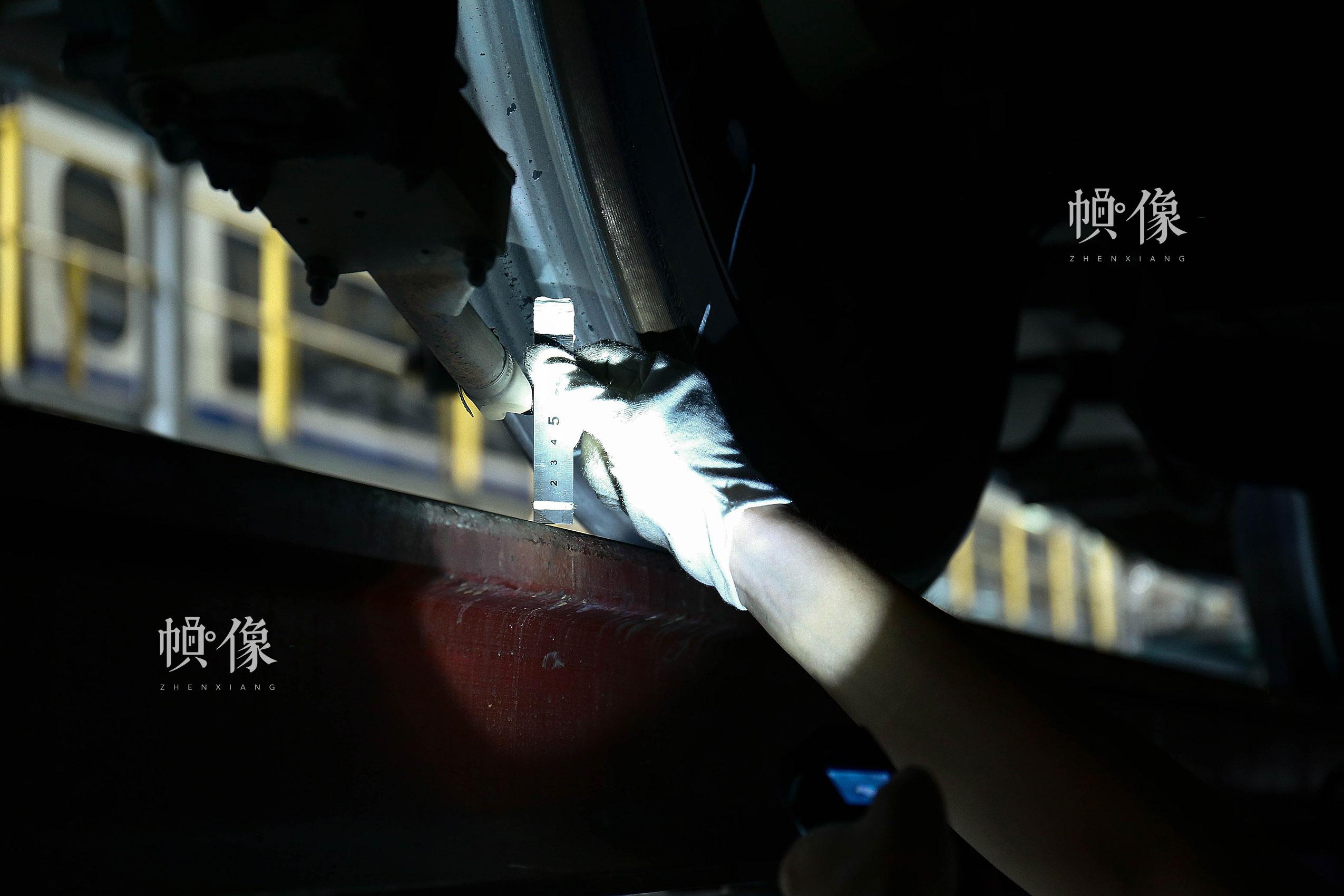 车辆行驶中需要利用撒砂系统增加轨面摩擦力,作业人员利用钢板尺测量撒砂管与轨道之间的高度。中国网记者 黄富友 摄