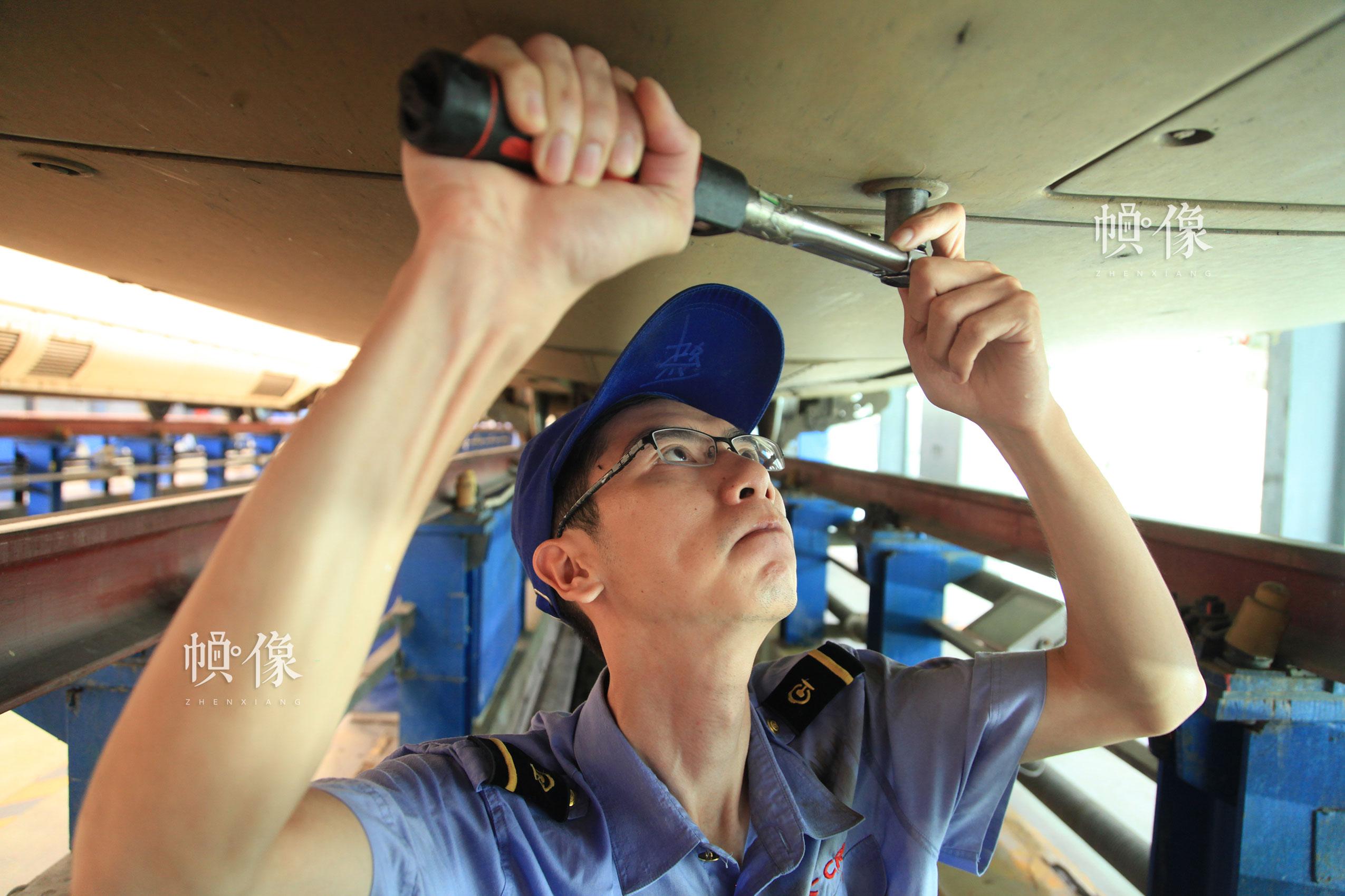 作业人员张朝舜进行车底螺栓扭力校验。北京动车段 李博 供图