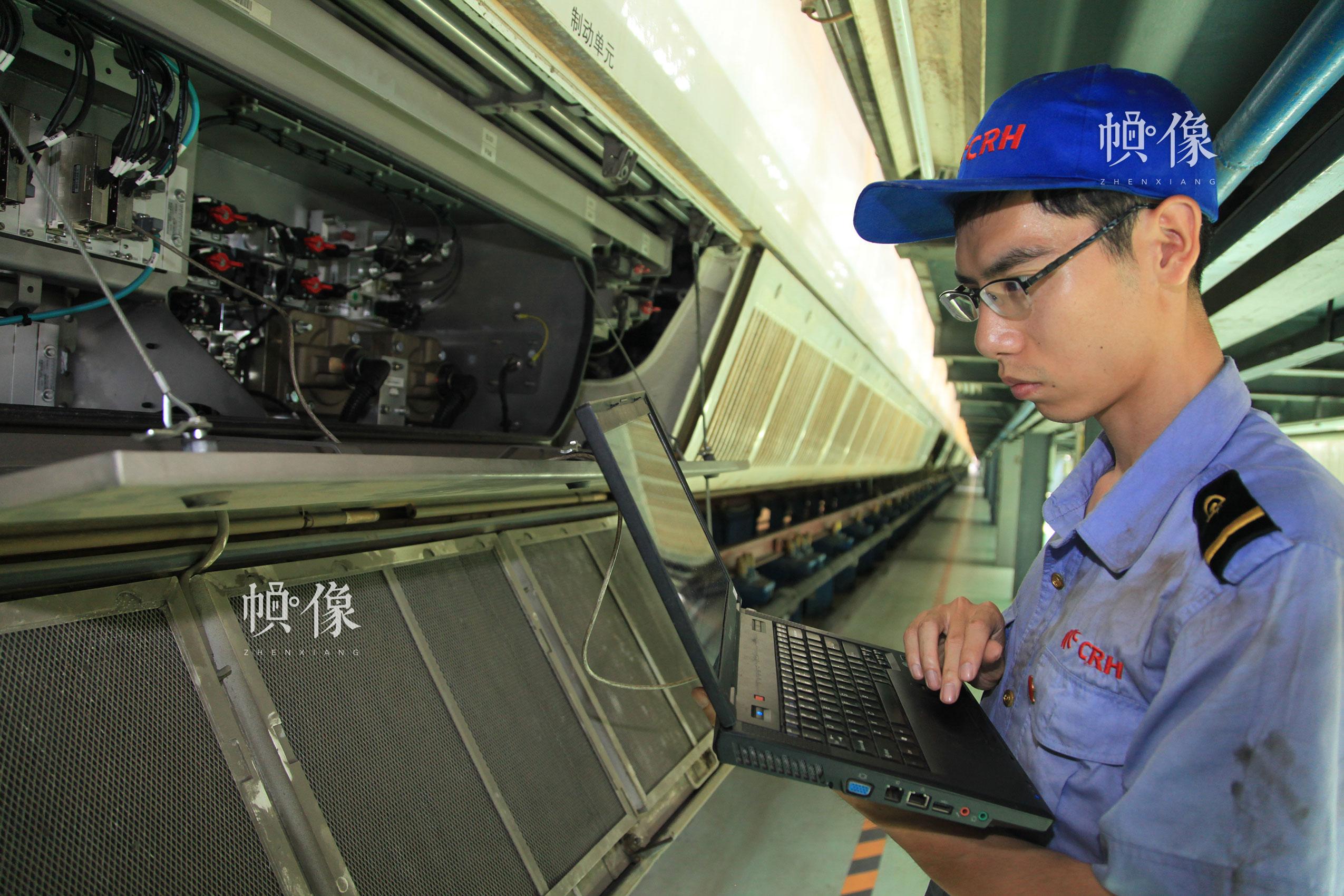 作业人员张朝舜进行动车组数据下载。北京动车段 李博 供图
