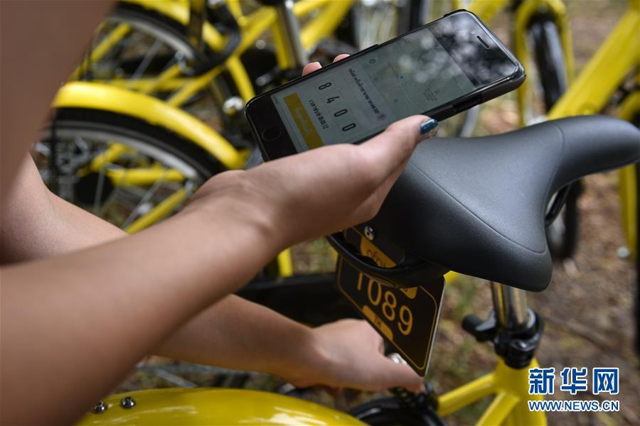 8月15日,在泰國曼谷的泰國國立法政大學,一名學生用手機解鎖ofo小黃車。