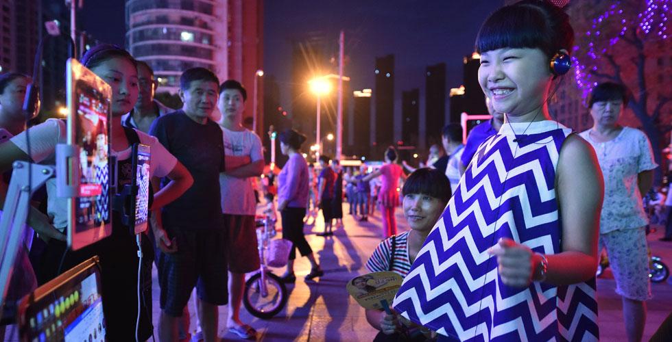 街头直播卖唱养家的8岁女孩