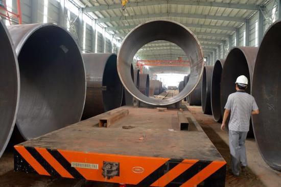 """资料图:2015年10月3日,这是在孟加拉国帕德玛大桥项目施工区域拍摄的一间厂房内的钢管(8月11日摄)。 由中国中铁大桥局中标承建的孟加拉国吉大港帕德玛大桥主桥长6150米,宽21.5米,是连接中国与东南亚的""""泛亚铁路""""的重要通道之一,也是中国海外中标的最大单体桥梁项目。新华社记者刘春涛摄"""