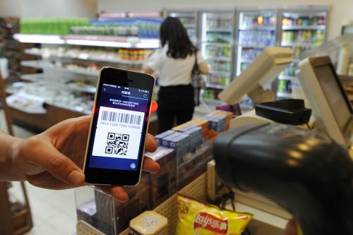 資料圖片:在杭州市區一家便利店內,一位顧客使用支付寶掃碼支付購買的商品。新華社記者 鞠煥宗 攝