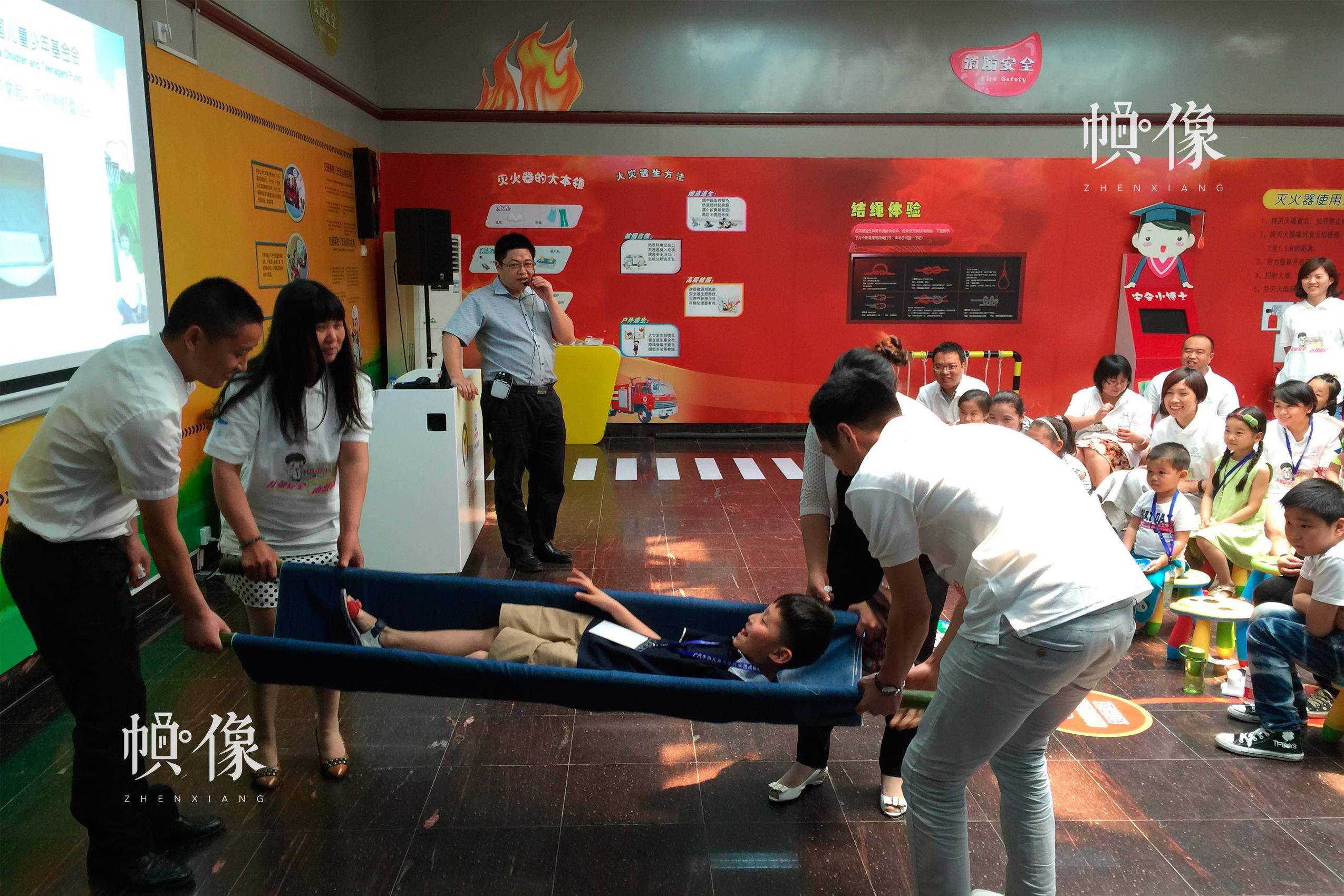 安全教育落地河南,在安全体验教室举办亲子活动,参与者体验简易担架制作与伤员搬运。中国儿童少年基金会供图