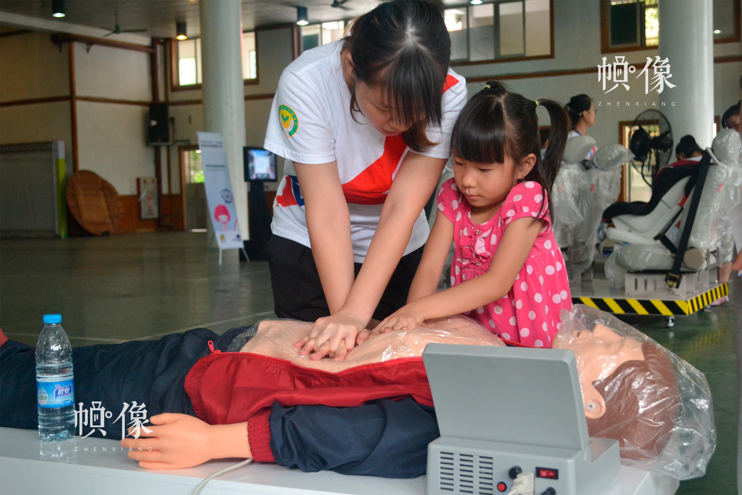 安全教育巡展活动依托社区为阵地,建设移动安全体验营,将安全教育送入社区、家庭身边。志愿者向小朋友示范心肺复苏。中国儿童少年基金会供图