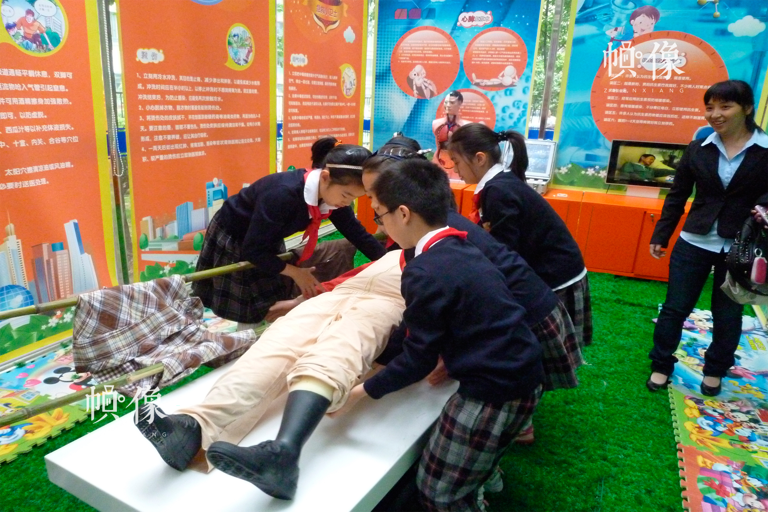 安全体验中心是在社区或校外活动场所建立的安全教育平台。在安全体验中心,学生进行简易担架制作和运送伤员的技能训练。中国儿童基金会供图