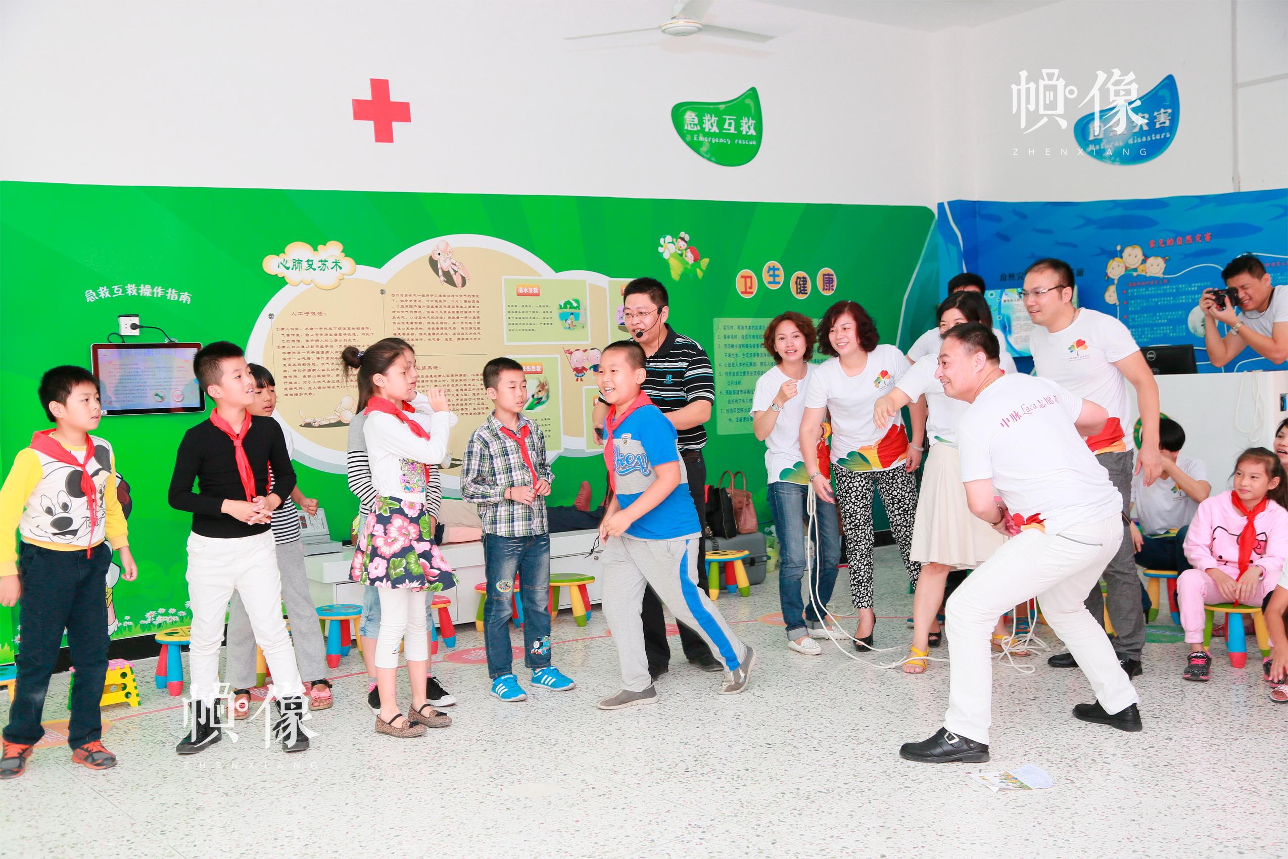 在安全体验教室中,组织亲子课堂,演示如何救助溺水者而进行的远岸救援。中国儿童少年基金会供图