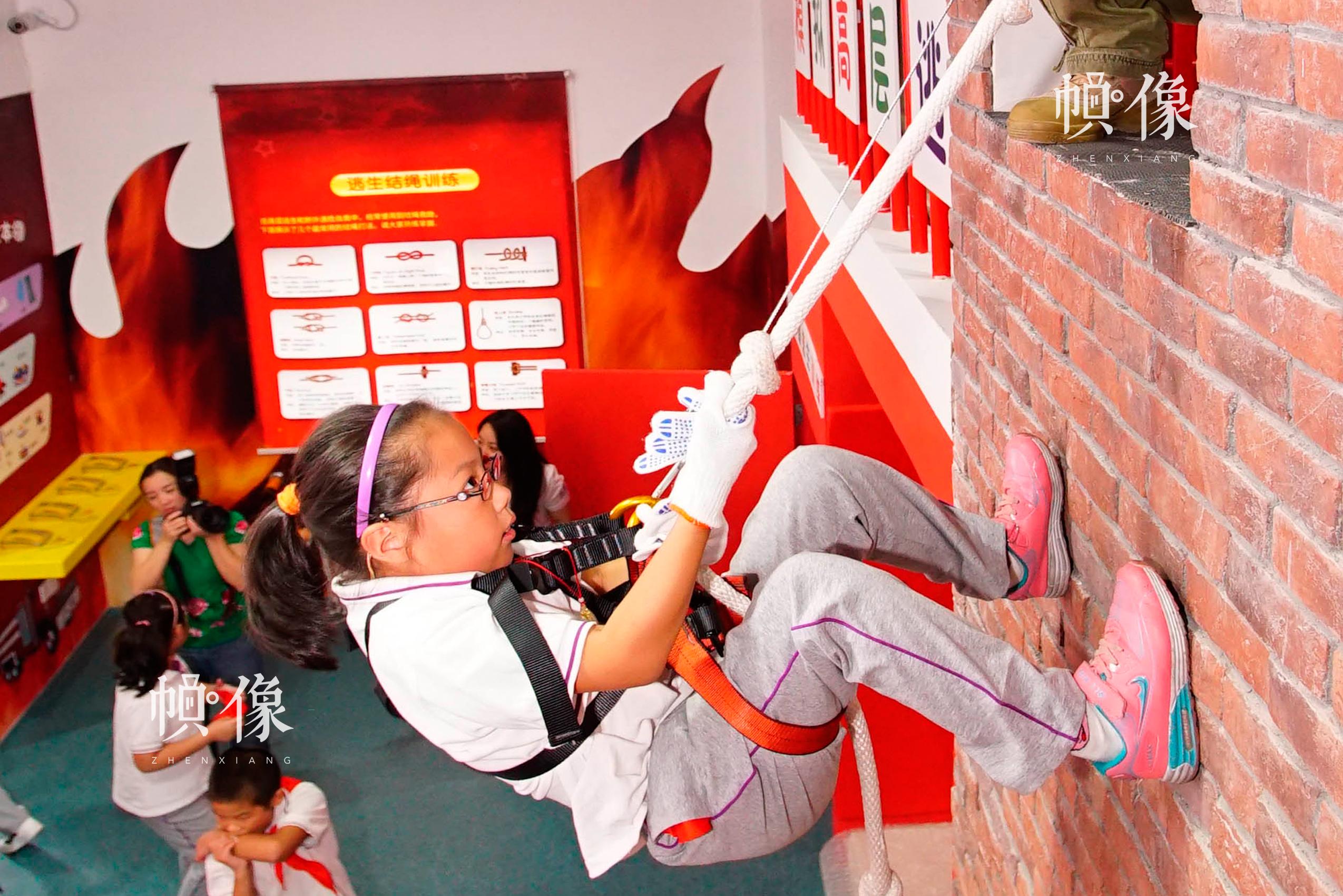 在安全体验中心,学生进行逃生避险之高空降落的应急技能训练。中国儿童少年基金会供图