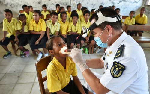 资料图片:2016年1月18日,在东帝汶首都帝力,中国海军152舰艇编队慰问队的医疗队员为孩子们进行健康检查。
