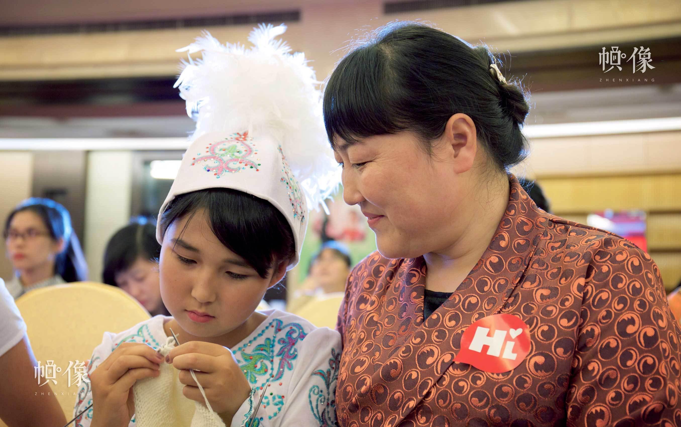 2017年8月28日,一位爱心妈妈正在和受助儿童互动织毛衣。中国网实习记者 李欣颖 摄