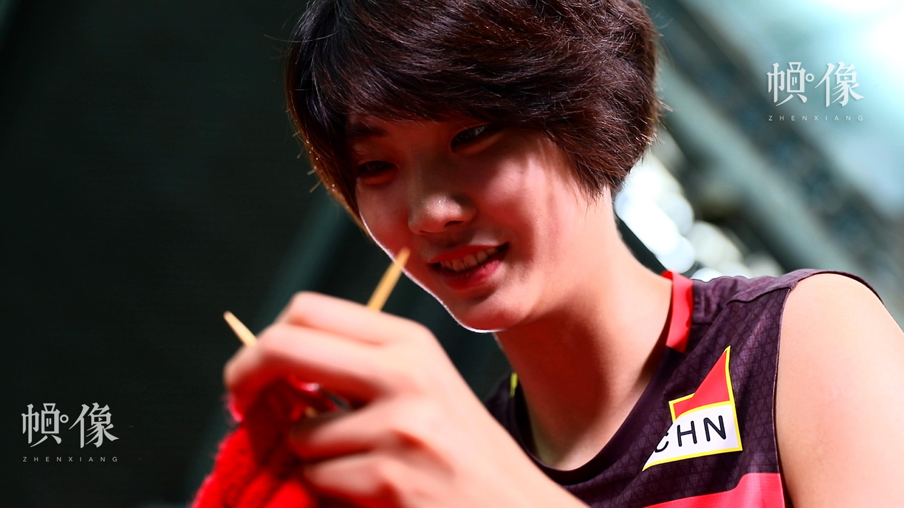 袁心玥织着毛衣脸上露出灿烂的笑容。中国儿童少年基金会供图。