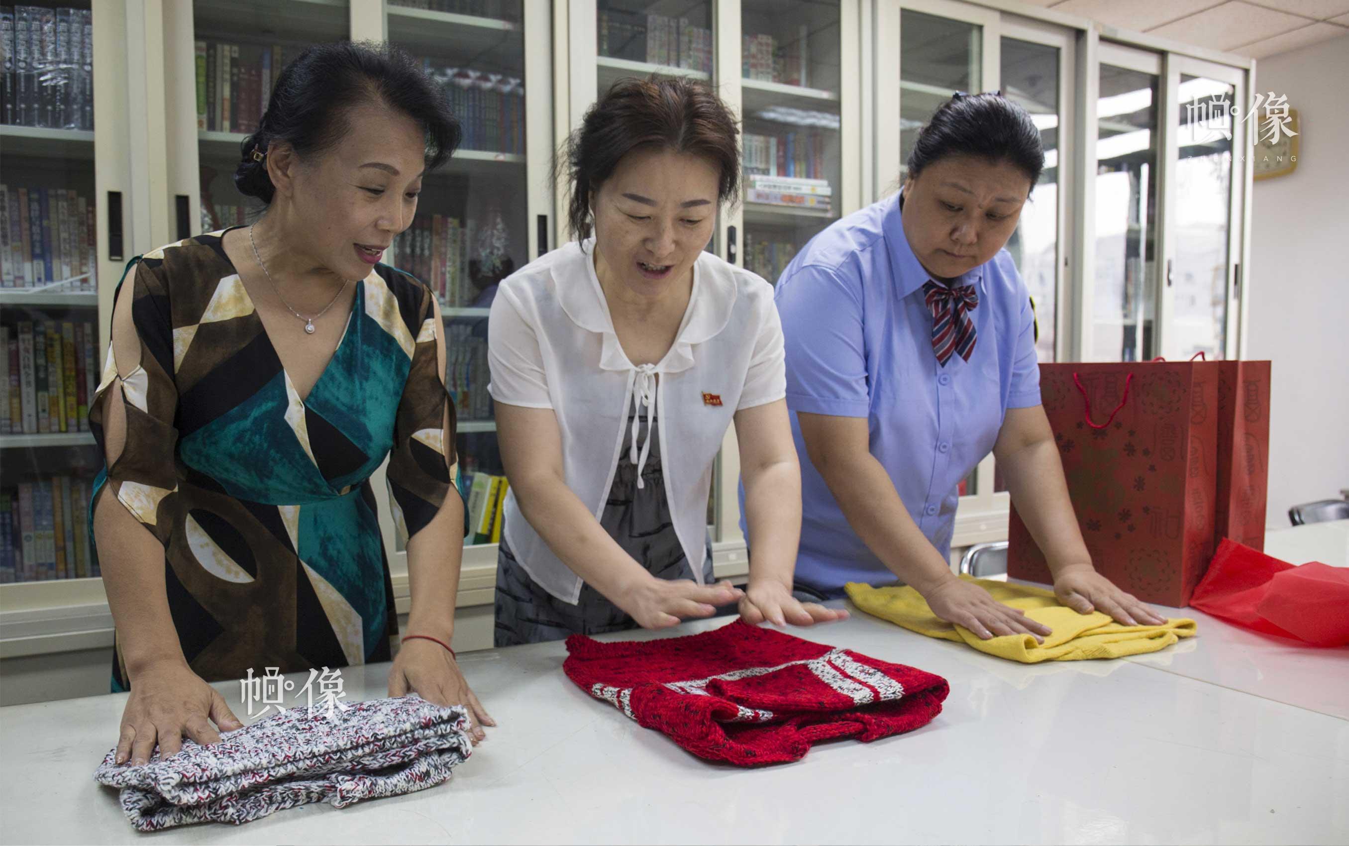 """2017年7月18日,李素丽(图左)和其他爱心妈妈把织好的毛衣装进袋子里,准备送往中国儿童少年基金会。据悉,2017年,""""恒爱毛衣""""总数将突破100万件。中国网实习记者 李欣颖 摄"""