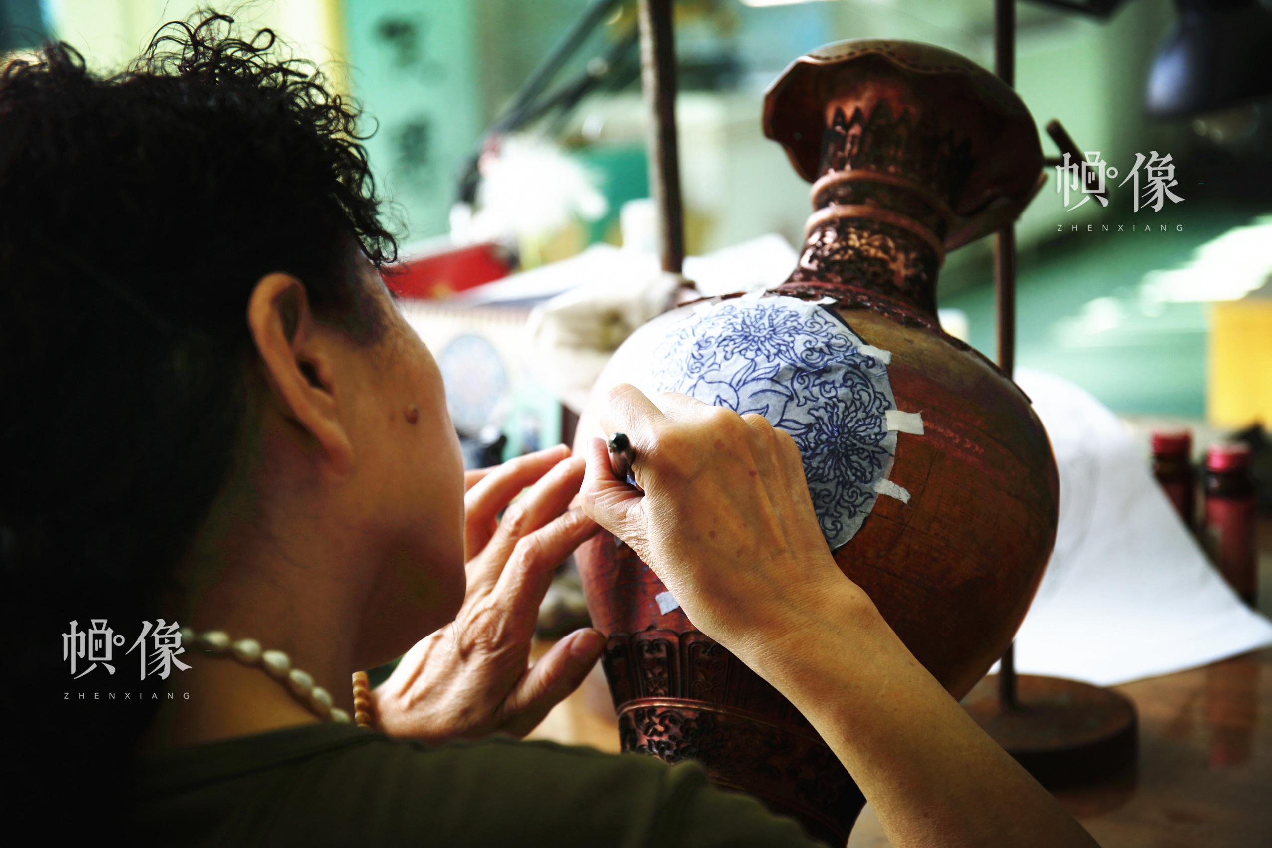 2017年9月5日,景泰蓝工匠把画好的图案沓在铜胚上。中国网记者 赵超 摄