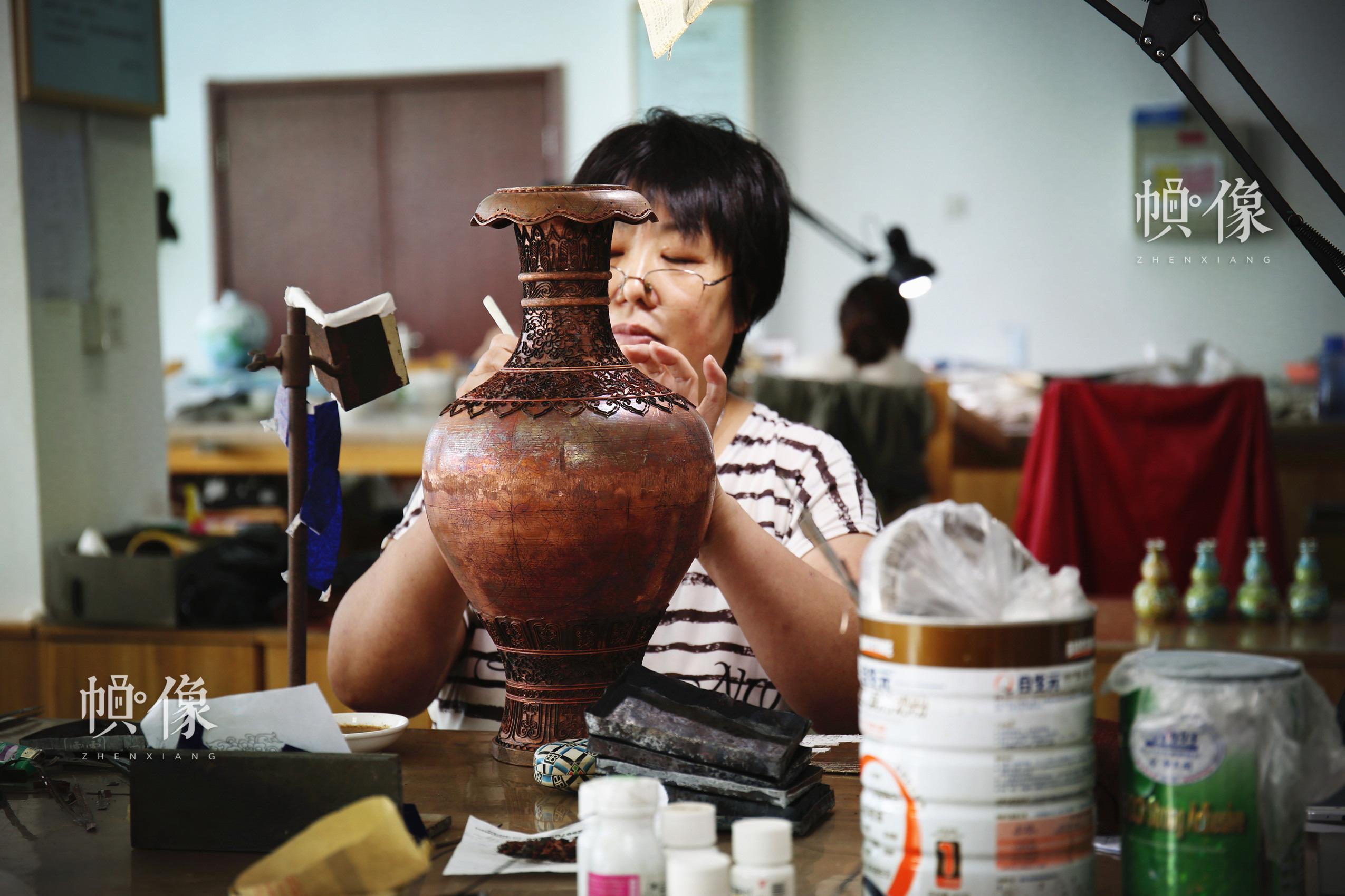 2017年9月5日,景泰蓝工匠将制作好的铜丝贴在铜胚上。中国网记者 赵超 摄