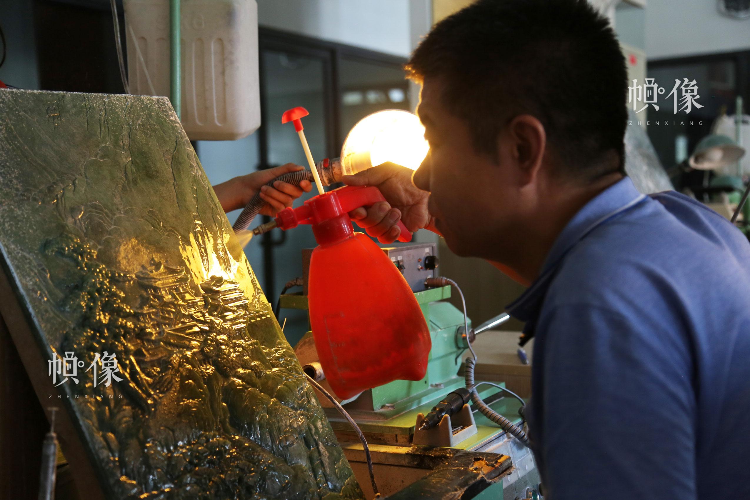 2017年9月5日,北京工美聚艺文化创意园区,中国玉雕大师张铁成用喷壶喷水去除玉雕画上的浮土。中国网记者 赵超 摄