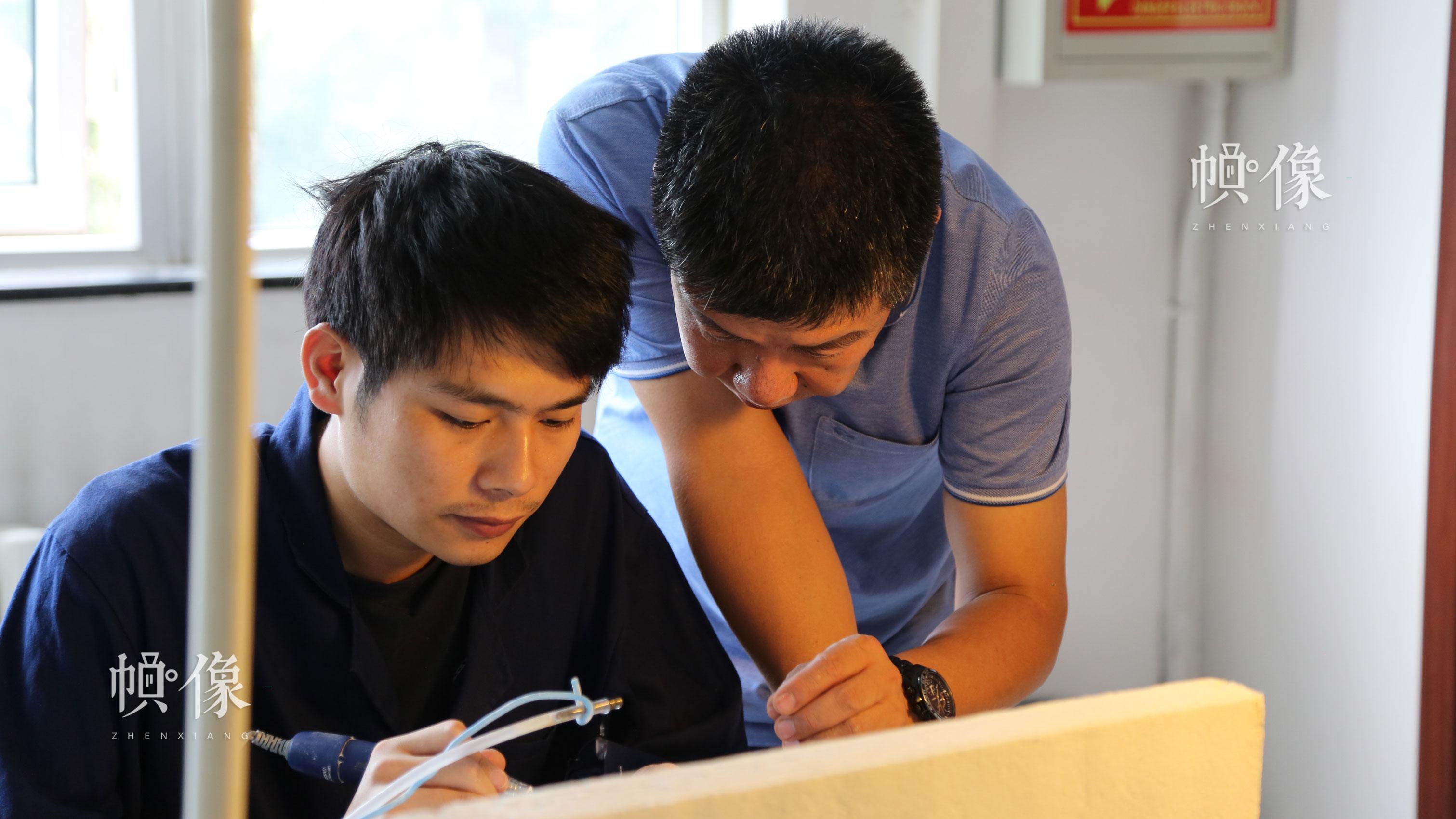 2017年9月5日,北京工美聚艺文化创意园区,中国玉雕大师张铁成指导徒弟雕刻玉器。中国网记者 赵超 摄