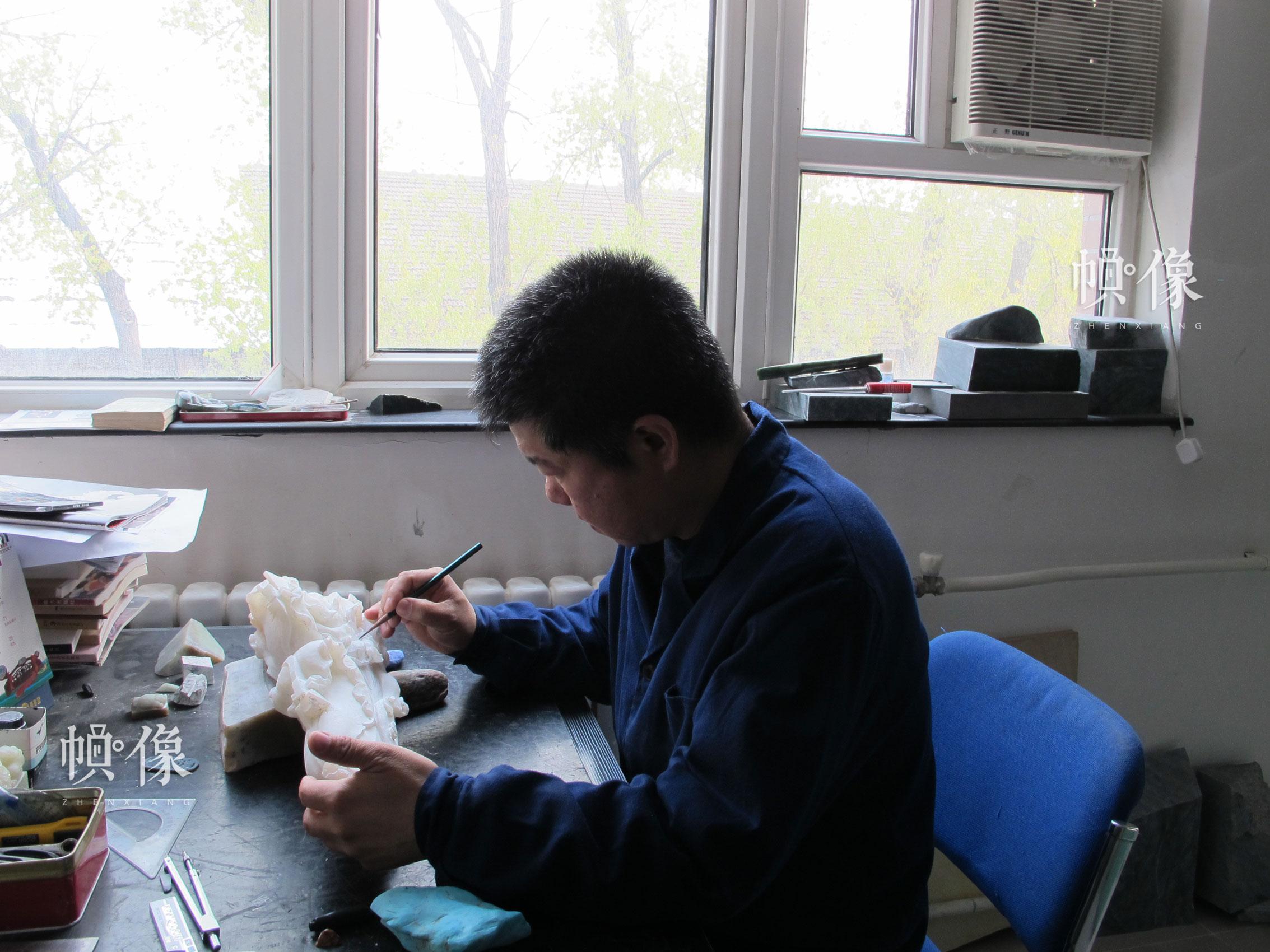 """张铁成大师正在雕刻""""白菜""""图形玉器。张铁成大师团队供图。"""