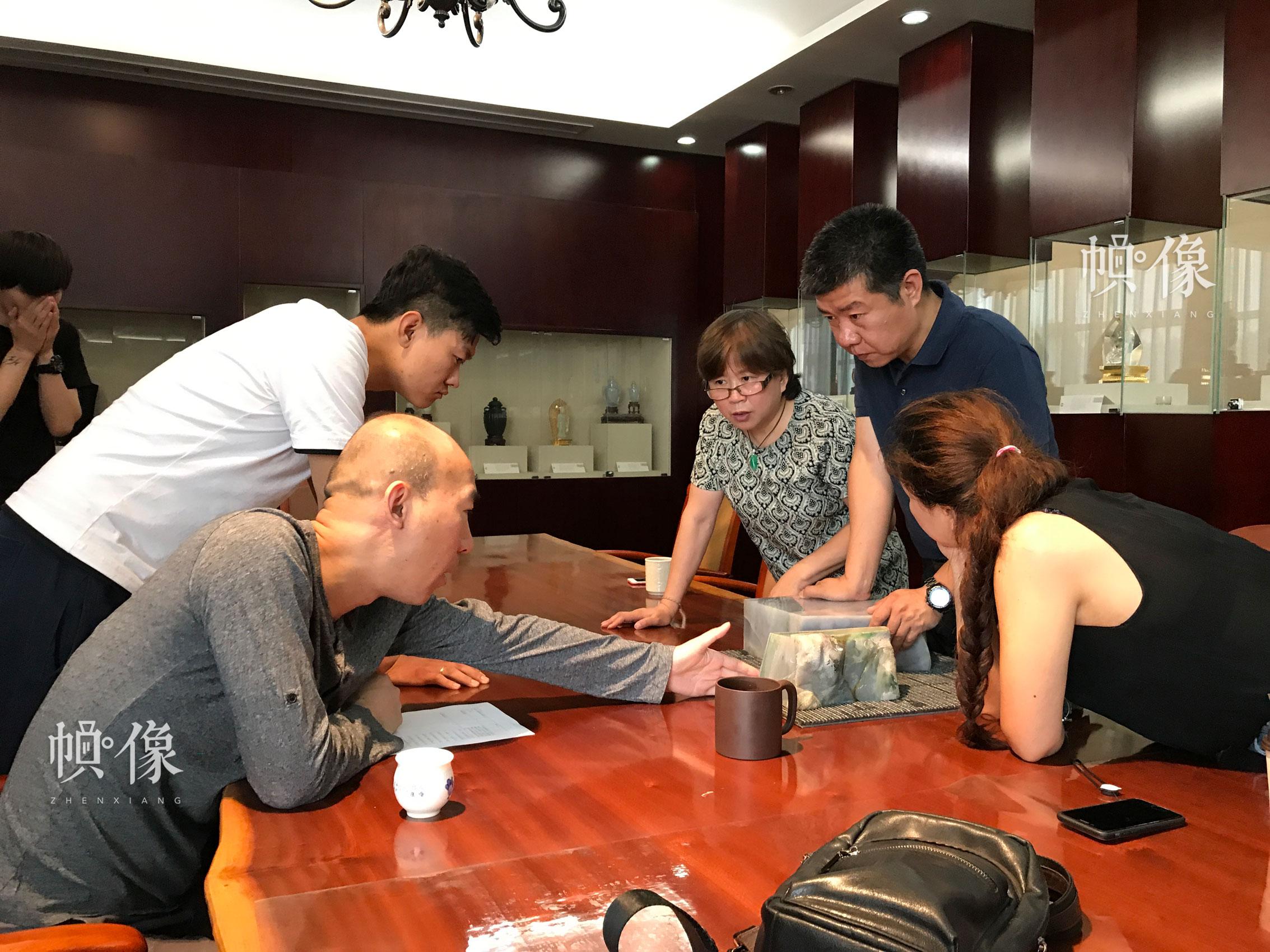 中国玉雕大师张铁成和团队成员就玉器雕刻进行讨论。张铁成大师团队供图