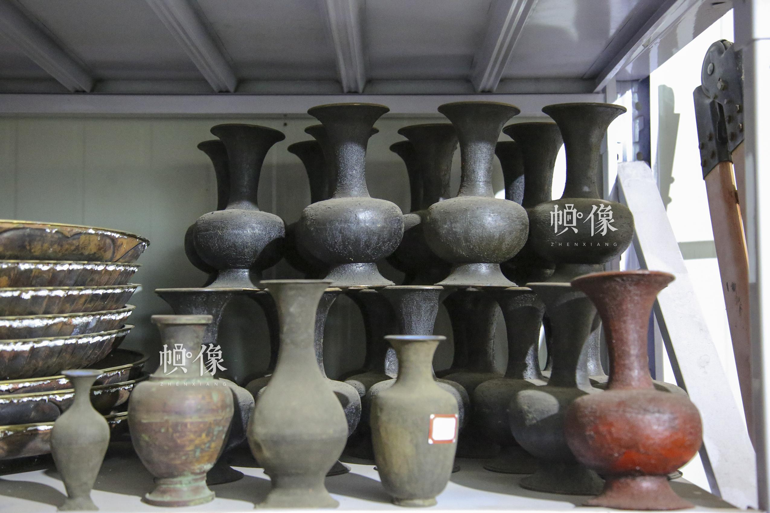 """2017年9月20日,""""明古斋""""雕漆工厂车间,用于制作雕漆的铜质胎具。由于铜材有压延性,可塑性,适宜于各种形体的制作;铜材硬中有软,又适合铜漆吻合的需要,且易于抛光擦拭,所以铜材成为制造雕漆内胎的最主要的原材料。使用铜料的雕漆制品,大都是瓶类、罐类、盒类、洗类、炉鼎熏类等,以圆体形的内胎为多数。中国网记者 黄富友 摄"""