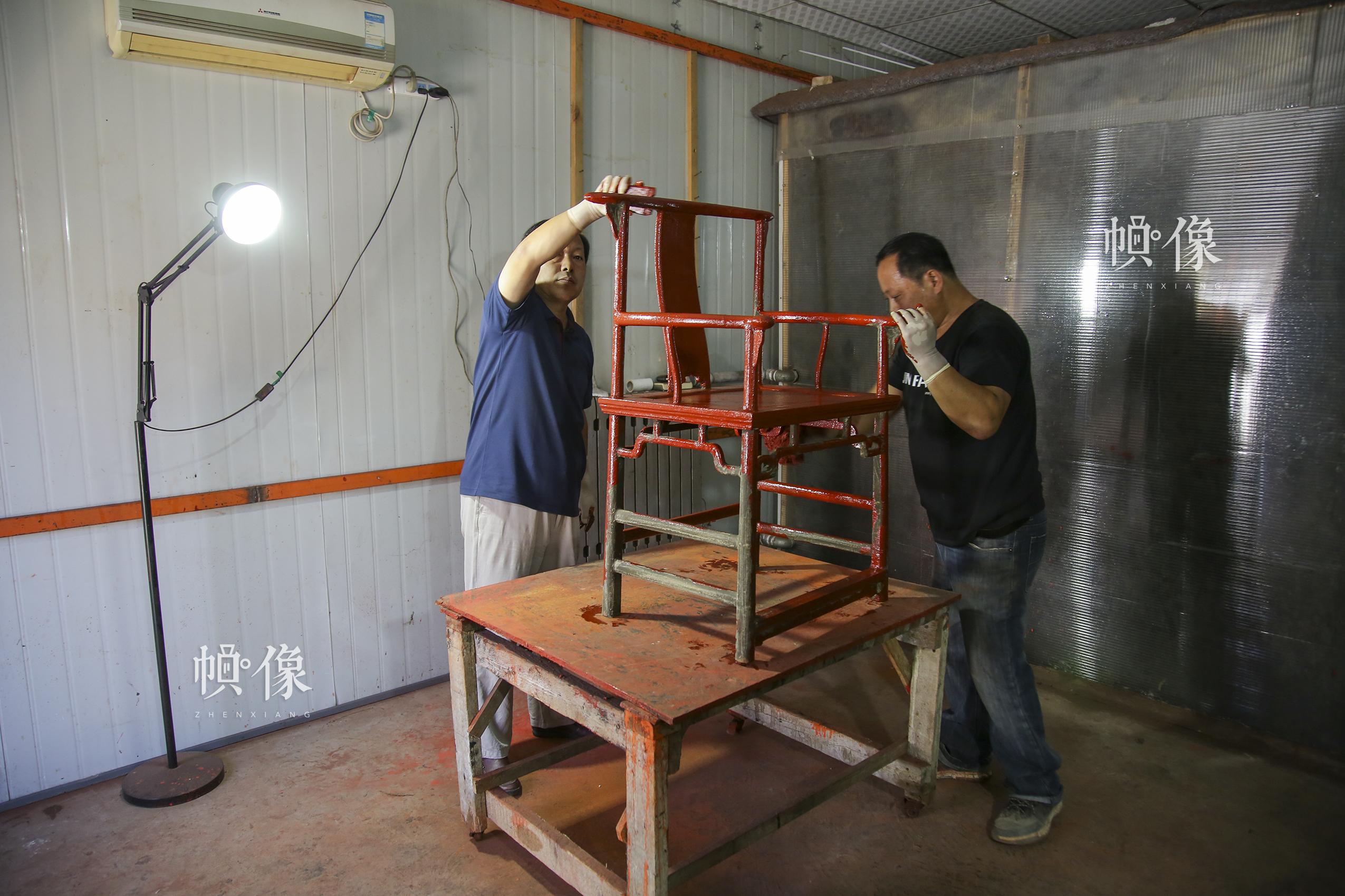 """2017年9月20日,""""明古斋""""雕漆工厂车间,北京工艺美术雕漆大师杨之新和同事给一把凳子髹漆。在做好的胎型上反复涂上漆层,称为光漆。第一层漆涂上阴干后,再涂第二层,每天涂一层,如此反复,达到工艺所需要的厚度为止。中国网记者 黄富友 摄"""