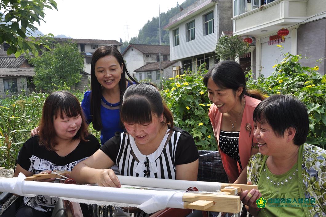 2015年夏天鎮巴縣殘聯工作人員現場觀摩賀小絨製作刺繡作品