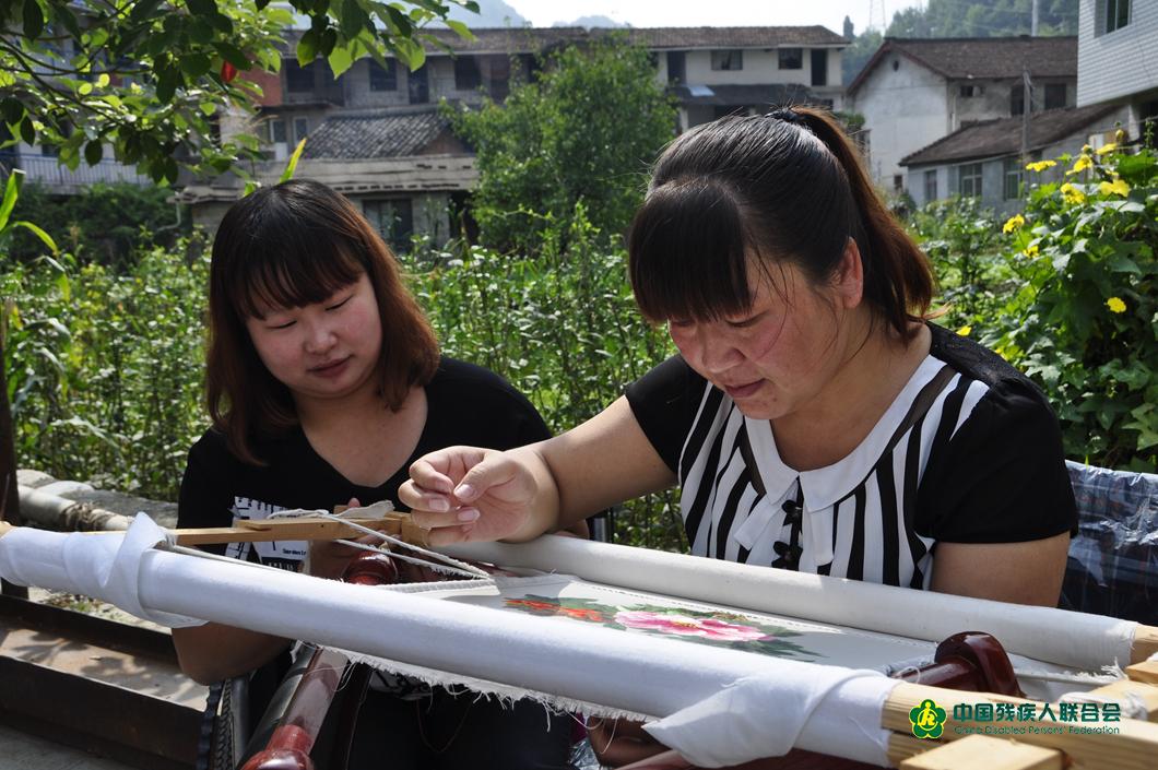 賀小榮為殘疾人講解刺繡技巧