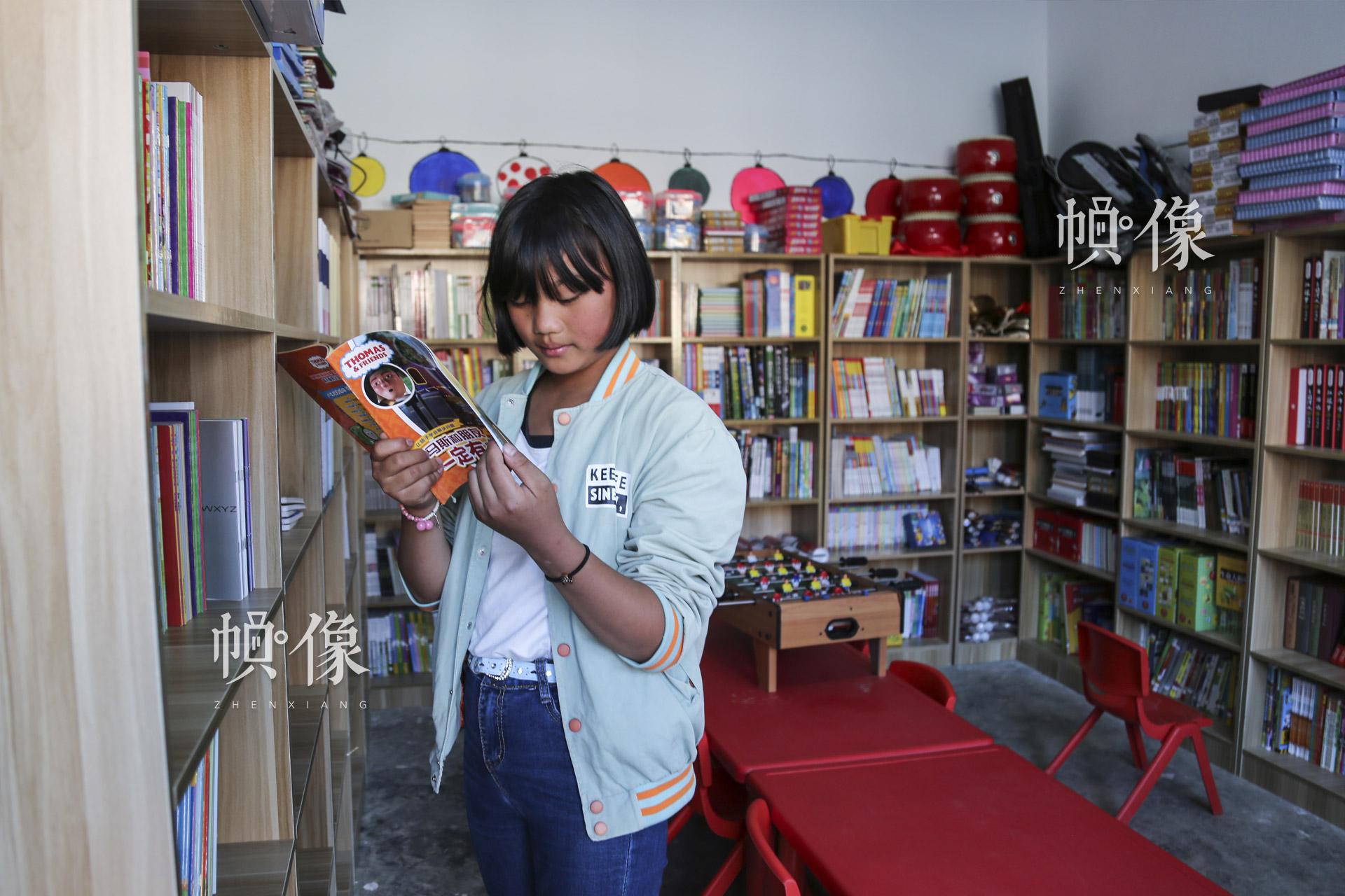 """肖欢欢喜欢看励志书籍和科学杂志。周末放假,在安马村""""儿童快乐家园""""的阅读室里经常能看到肖欢欢。中国网记者 黄富友 摄"""