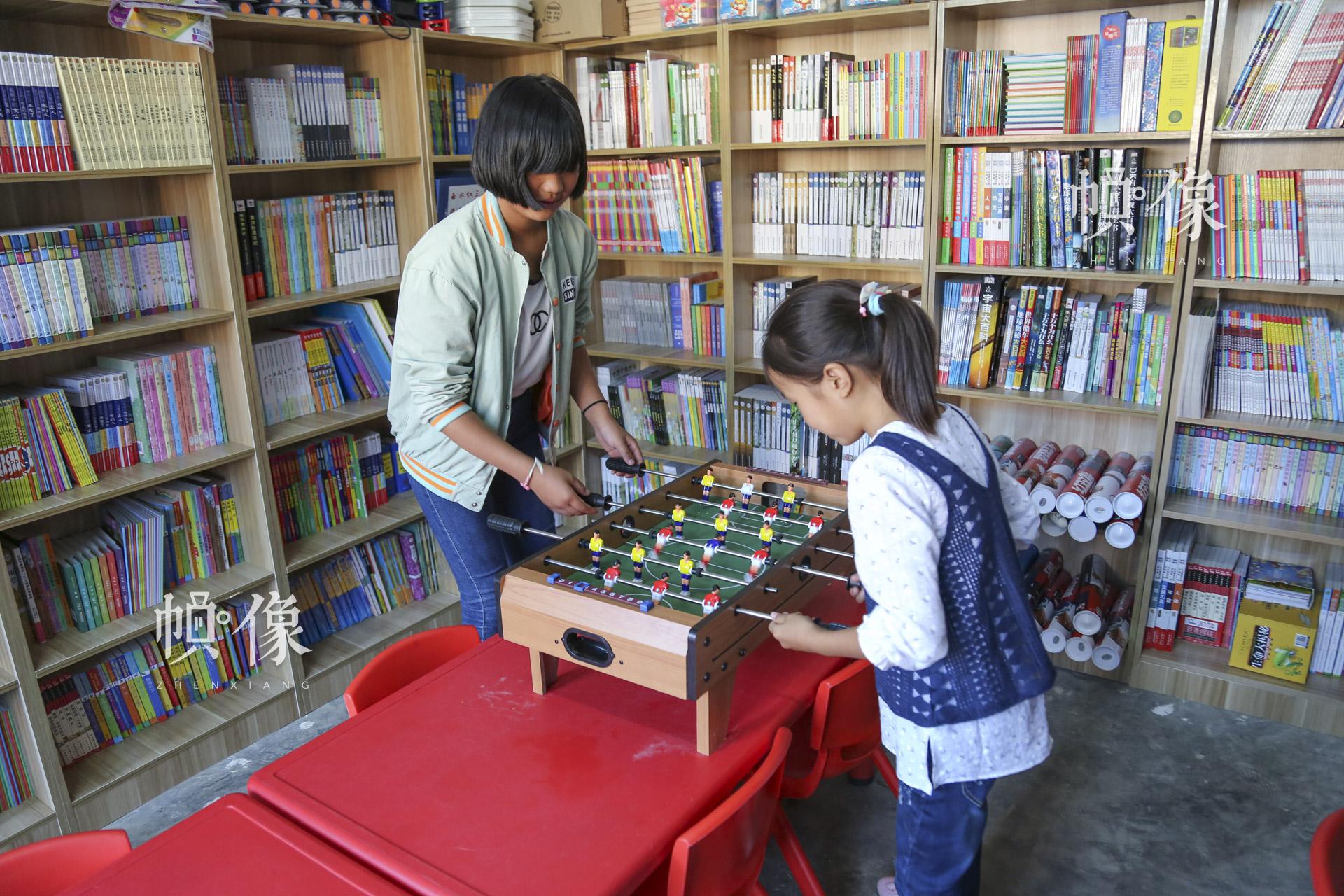 """肖欢欢和金子涵在儿童快乐家园玩桌游。""""这里有很多的图书,还有很多的玩具,每天都有很多的小朋友来这里玩,我就感到非常的开心、欢乐。""""肖欢欢说。中国网记者 黄富友 摄"""