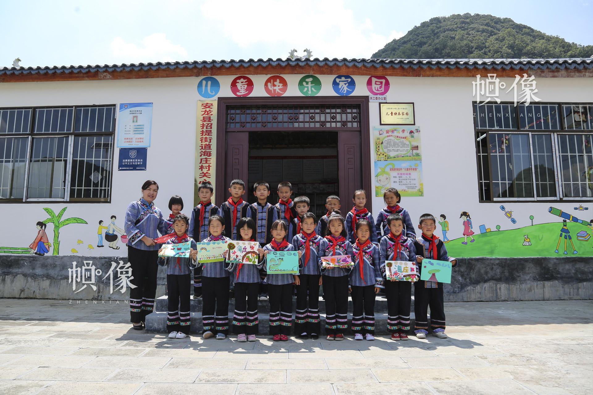 """余梅老师与罗天梁等留守儿童在""""儿童快乐家园""""合影。余梅说,""""这些孩子缺的是那份爱,希望更多的人来关心他们,来爱他们,给他们温暖。""""据安龙县妇联主席戴江介绍,仅安龙县三个""""儿童快乐家园""""的留守儿童就有536个。中国网记者 黄富友 摄"""