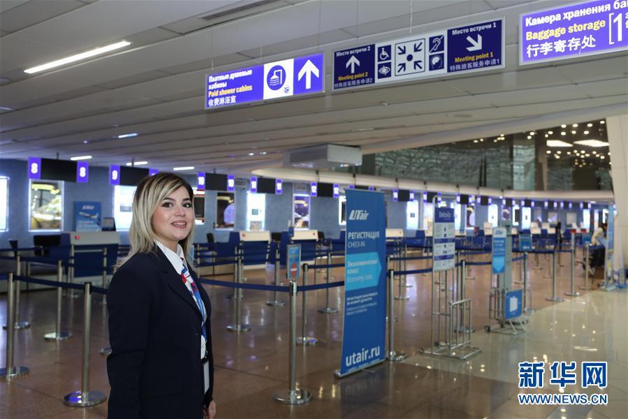 10月11日,在白俄罗斯明斯克机场,一名工作人员从有中文标识的指示牌下经过。