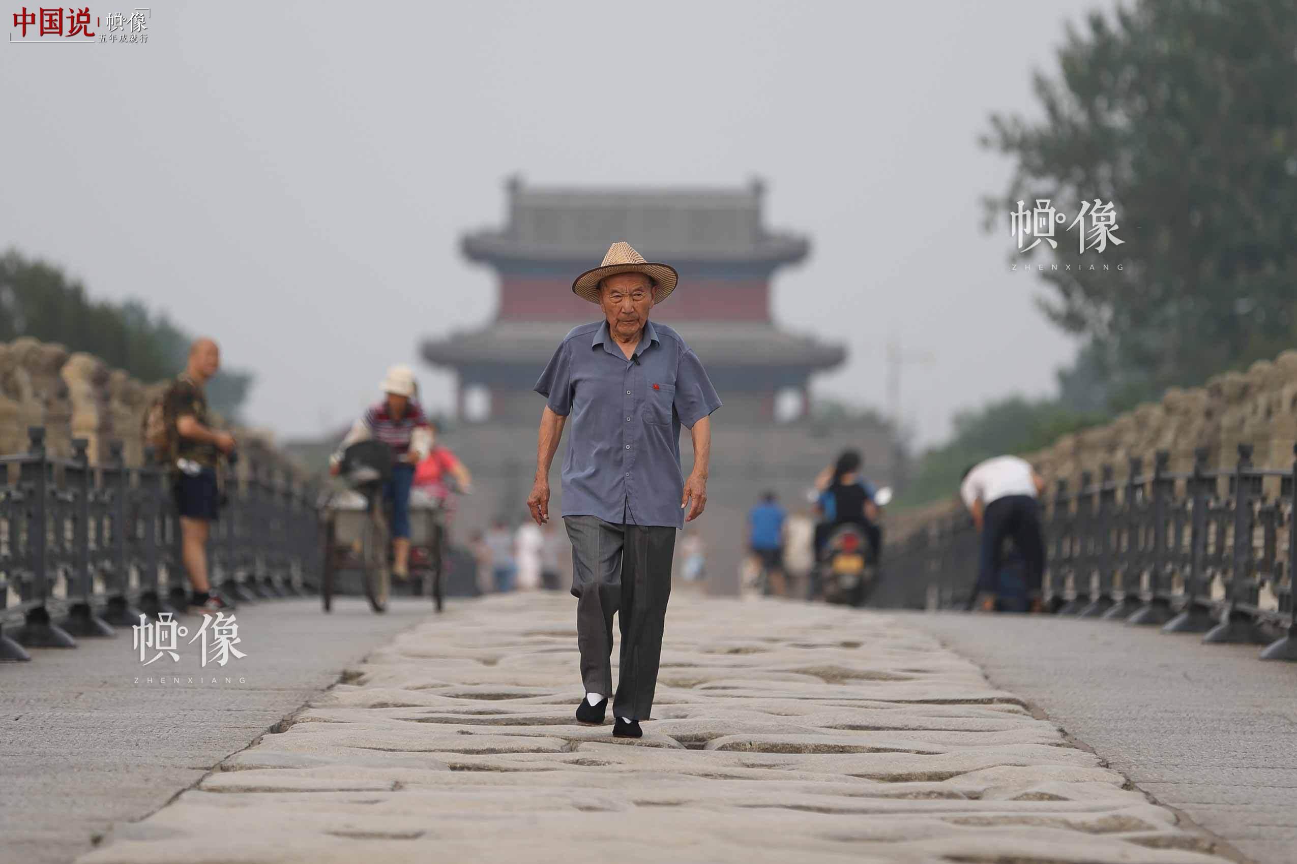 """86岁的郑福来走在卢沟桥的石板路上。出生于1931年的郑福来,是80年前卢沟桥事变的亲历者。这座全长266.5米的桥,是郑福来儿童时期的嬉戏""""游乐园"""",少年时期的亡国""""屈辱地"""",以及相伴至今的""""精神家园""""。中国网记者 陈维松 摄"""
