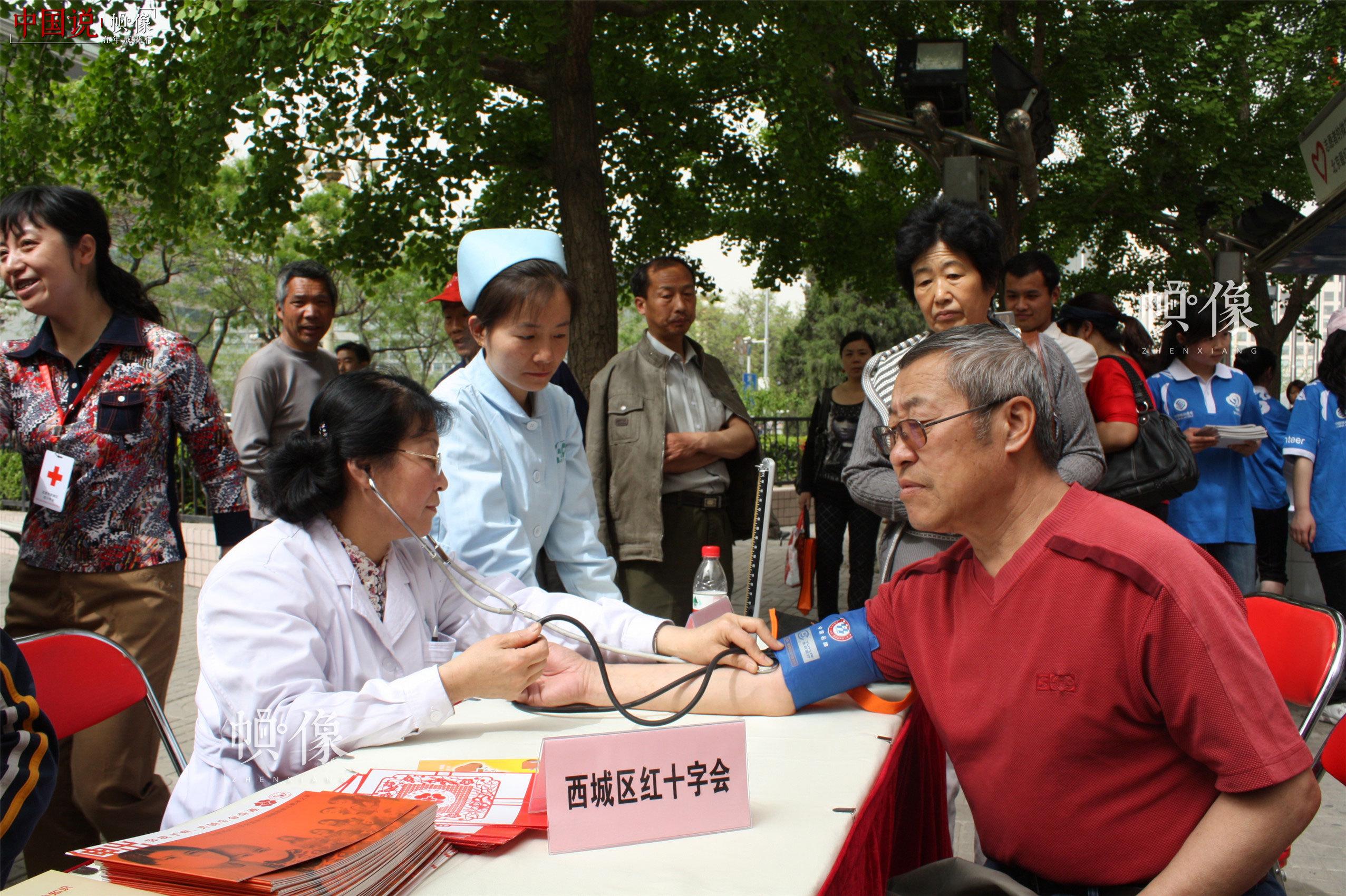 """2010年5月7日,西城区红十字会开展""""五八""""红十字日宣传活动,红十字志愿者为市民进行街头义诊。(西城区红十字会供图)"""