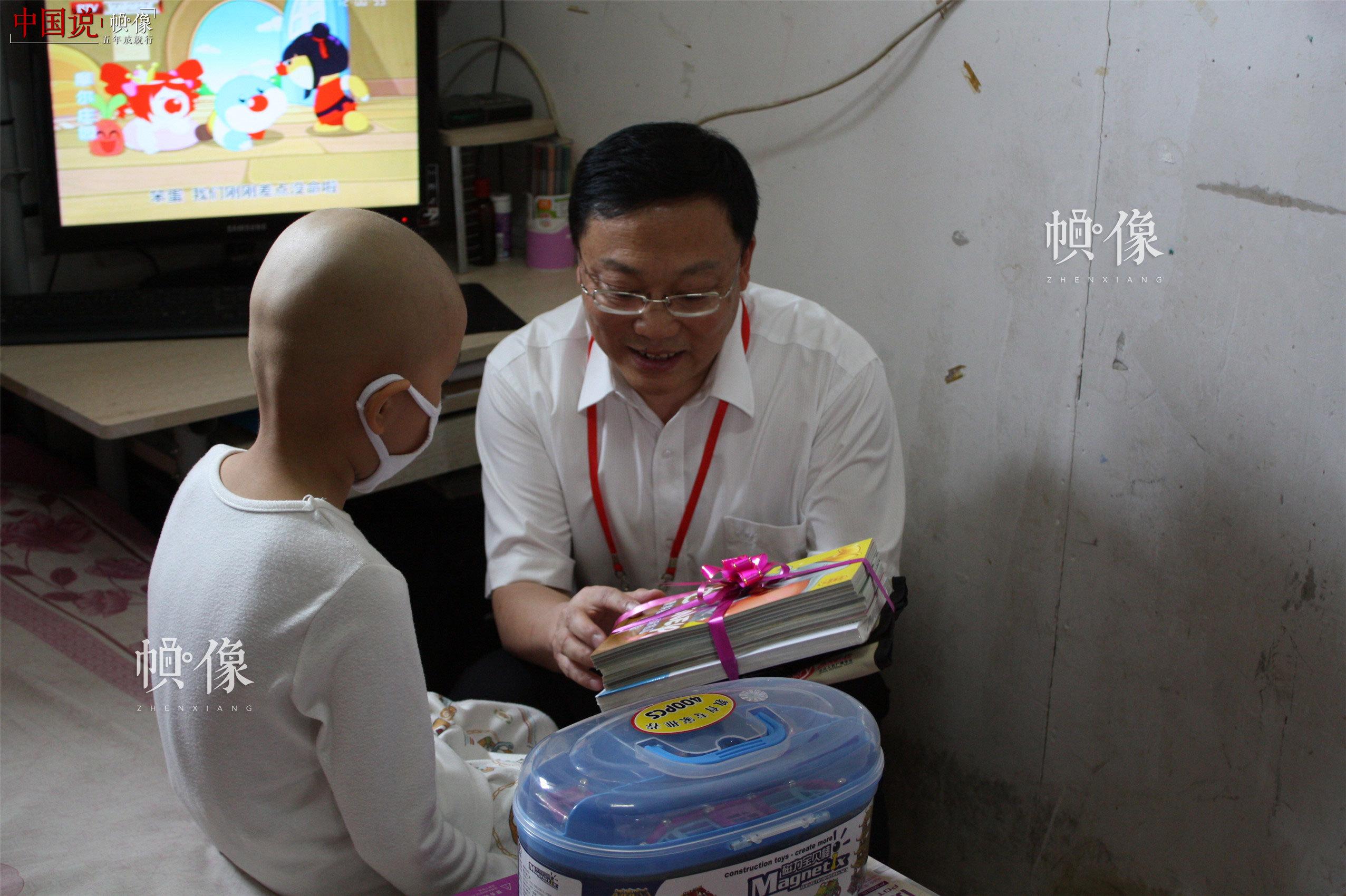 """2012年""""六·一"""",西城区红十字会常务副会长王志东慰问患""""大病""""儿童。(西城区红十字会供图)"""