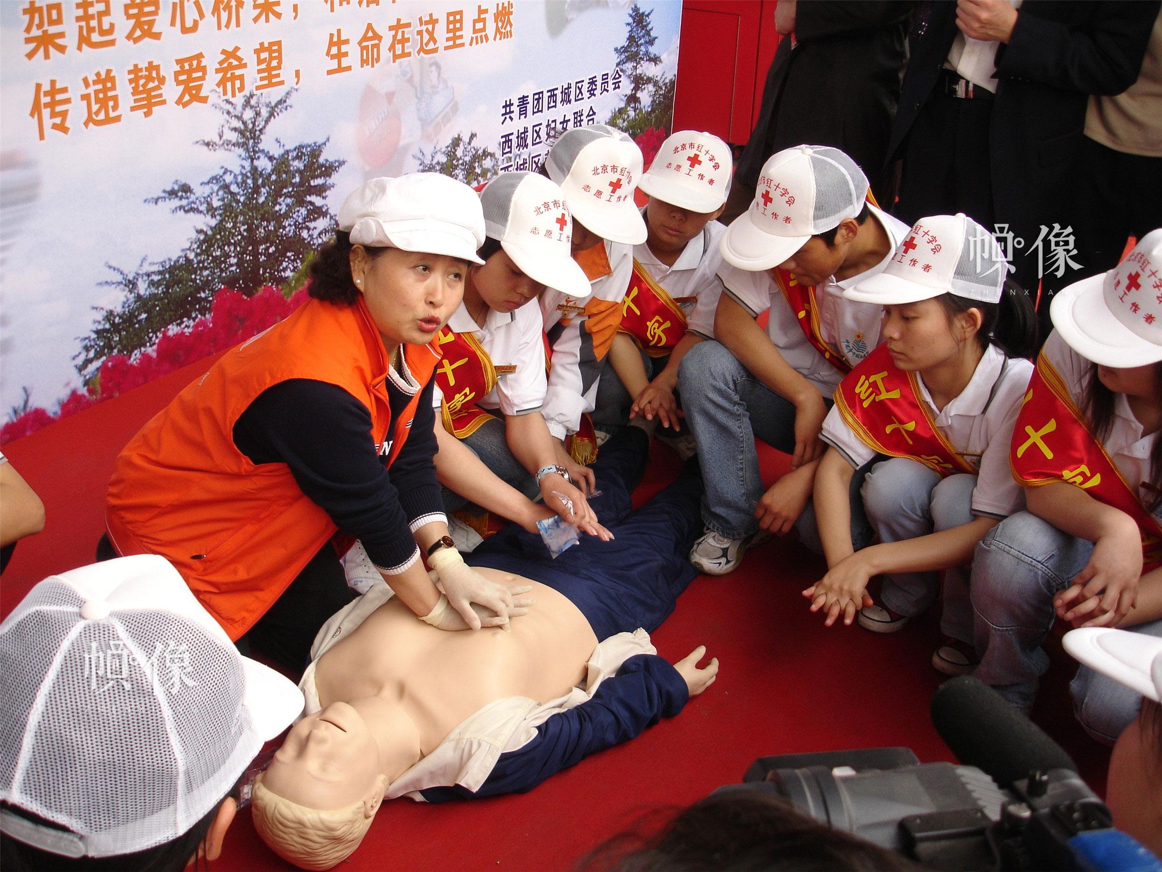 """2006年5月7日,西城区红十字会在西单开展""""五八""""红十字日宣传活动,图为老师为过往群众和志愿者介绍应急救护知识。(西城区红十字会供图)"""