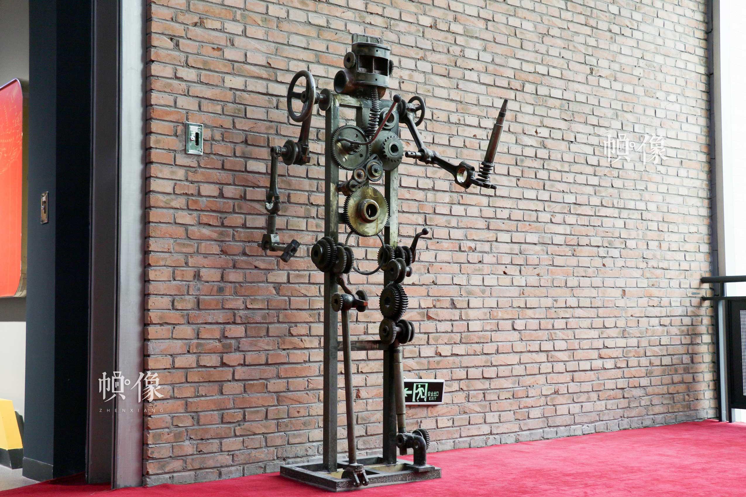 朝阳规划艺术馆主展区一角,由厂房遗留废旧螺丝、齿轮等零部件组装而成机器人模型。中国网记者 赵超 摄