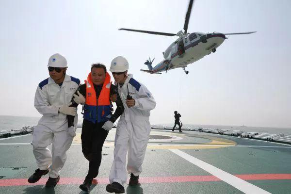 """▲救援直升机在演练中将""""受损船只""""上的群众转移至救援船上。(新华社)"""