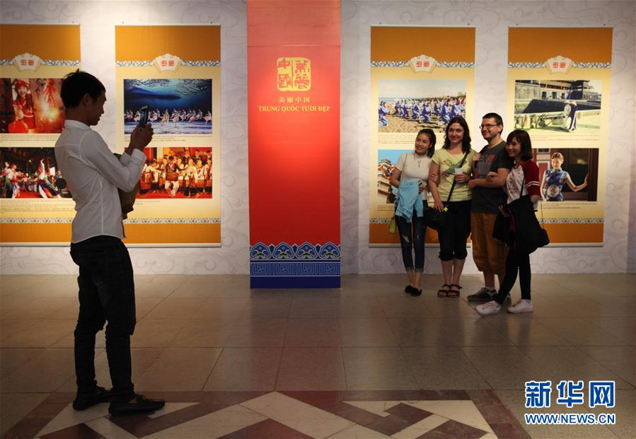 """11月6日,在越南首都河内,观众在参观""""美丽中国美丽越南""""图片展时合影留念。"""