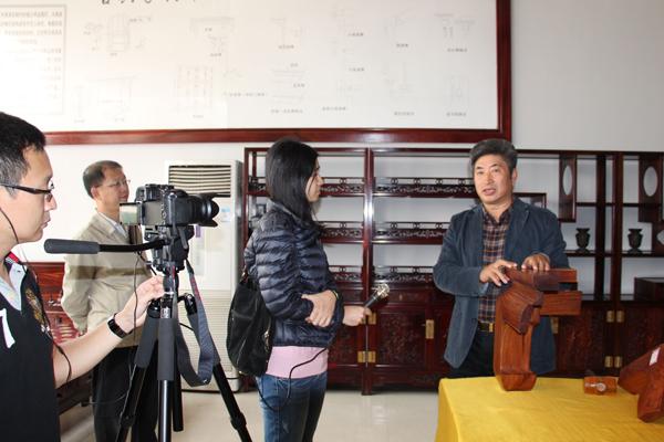 叶双陶向记者展示红木家具之榫卯结构