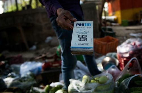资料图片:2017年4月12日,在印度新德里街头,一名蔬菜摊主手持Paytm二维码接受电子支付。印度Paytm在支付宝母公司蚂蚁金服的支持下,已经成为印度最大的移动支付平台。新华社记者 毕晓洋 摄