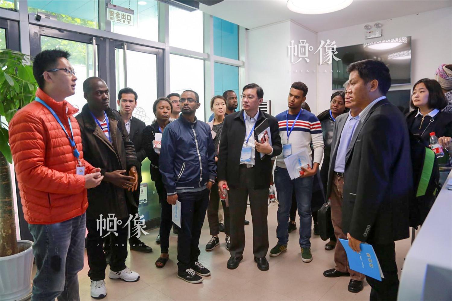 """2017年10月15日上午,由政府间""""南南合作""""项目支持,应国家卫生计生委邀请,来自非洲、东南亚国家的19名艾滋病防治机构领导和代表在中国疾控中心艾防中心合作室张大鹏主任的陪同下,参观访问了淡蓝公益检测室。代表团一行对移动智能技术与艾滋病防治结合表现出强烈兴趣,双方就快速检测、Blued预约平台、感染者转接、信息安全保护等问题进行了深入交流。淡蓝公益 供图"""