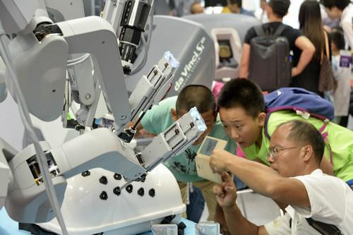 资料图片:在北京举行的2017年世界机器人大会上,观众在观看展出的外科手术机器人(8月23日摄)。新华社记者 李欣 摄
