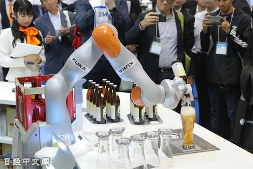 资料图片:德国库卡的机器人在倒啤酒。(《日本经济新闻》网站)