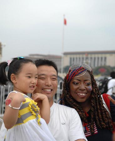 Un Chinois et sa fille posent avec une touriste américaine sur la Place Tian'anmen au coeur de Beijing.
