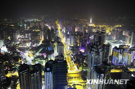 Au moment où l'on allume les lampes, les voitures roulent dans le centre ville de Shenzhen où se dressent de nombreux immeubles, ce qui forme une féerie de lumière.