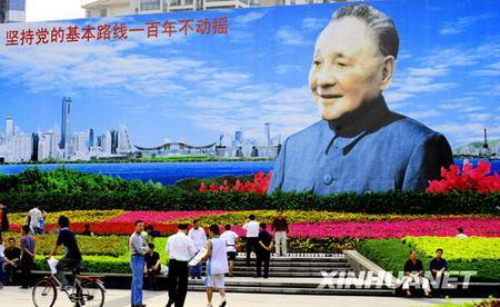 Les habitants flânent sur la place devant le portrait de Deng Xiaoping, sur l'avenue Shennan, dans la ville de Shenzhen.
