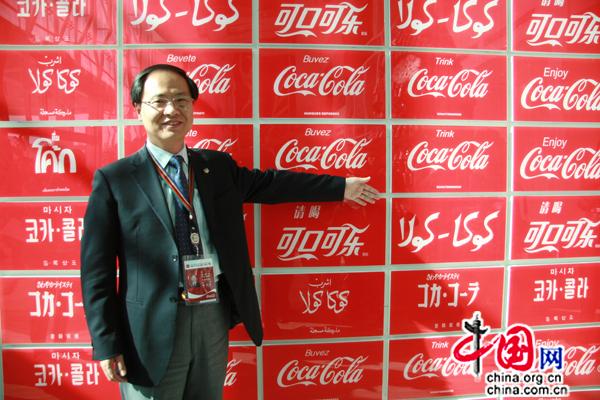 Les logos de Coca-Cola en différentes langues. M.Chen montre la version chinoise et la version en langue ouïgoure aux journalistes.